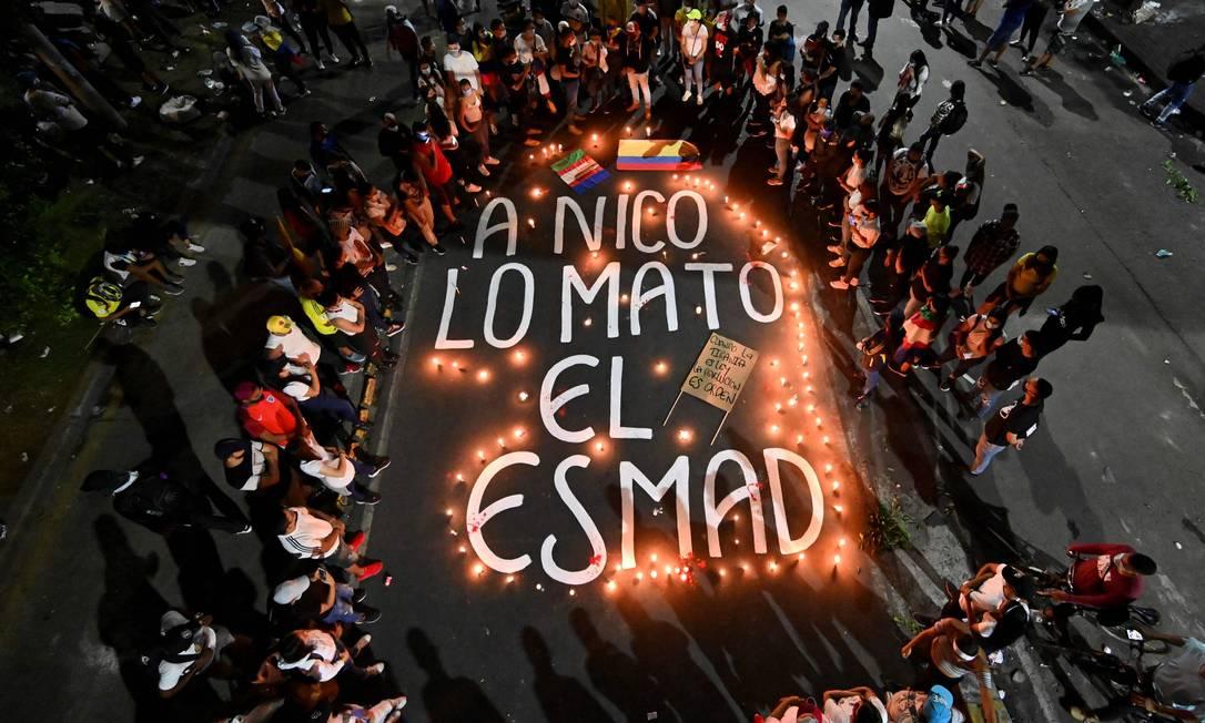 """Parentes e amigos de Nicolas Guerrero, morto durante confrontos com a tropa de choque em um protesto contra um projeto de reforma tributária, se reúnem em torno de velas em torno das palavras """"Nico foi morto pela ESMAD"""" (""""Escuadron Movil Antidisturbios"""", tropa de choque da polícia nacional), durante uma vigília em sua homenagem, em Cali Foto: LUIS ROBAYO / AFP"""