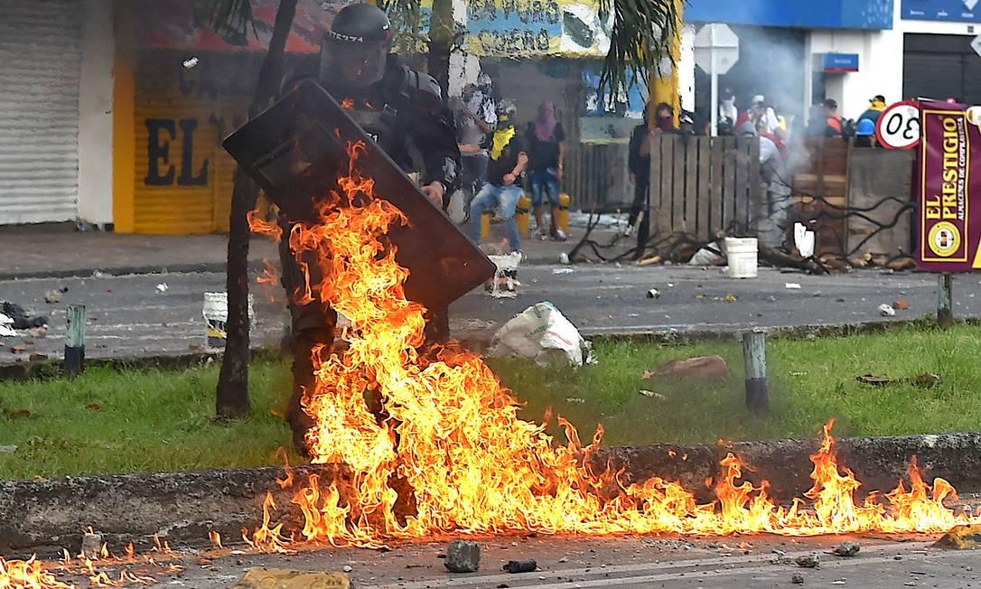 Policial de choque é atingido por coquetel molotov lançado durante confrontos com manifestantes Foto: LUIS ROBAYO / AFP