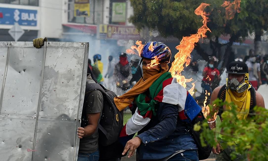 Manifestante é atingido por um coquetel molotov lançado durante confrontos com policiais de choque durante um protesto contra uma proposta de reforma tributária do governo em Cali Foto: LUIS ROBAYO / AFP