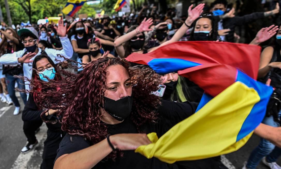 Manifestantes dançam durante um protesto contra um projeto de reforma tributária lançado pelo presidente Ivan Duque, em Medellín, Colômbia| Foto: JOAQUIN SARMIENTO / AFP