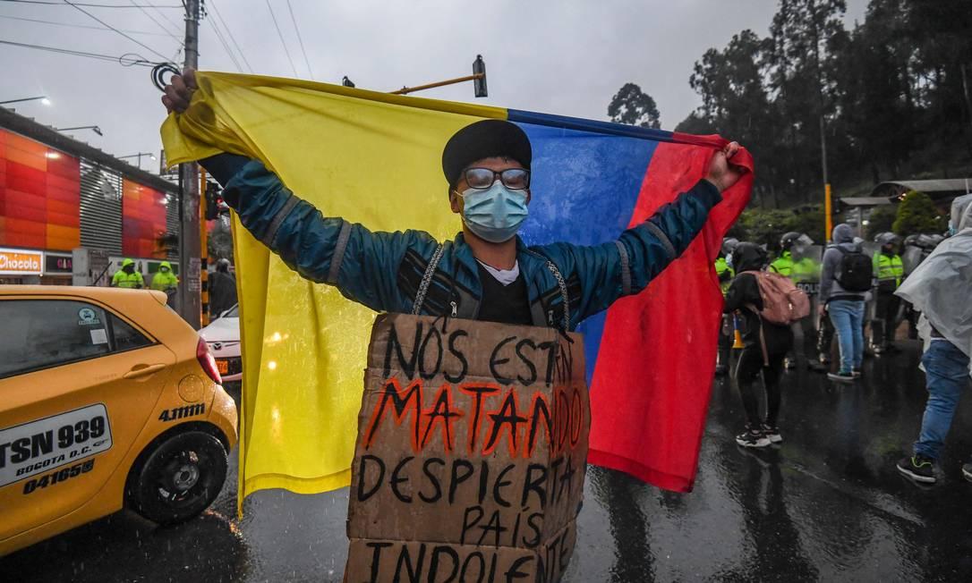 """""""Estão nos matando, desperta, país indolente"""", diz cartaz de manifestante que mar segurando bandeira nacional, em Bogotá Foto: JUAN BARRETO / AFP"""