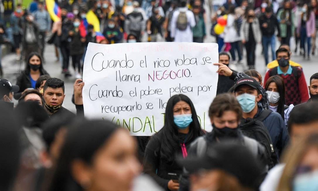 """""""Quando o rico rouba se chama negócio. Quando o pobre luta para recuperá-lo é chamado de vândalo"""", diz cartaz de manifestante em Bogotá Foto: JUAN BARRETO / AFP"""