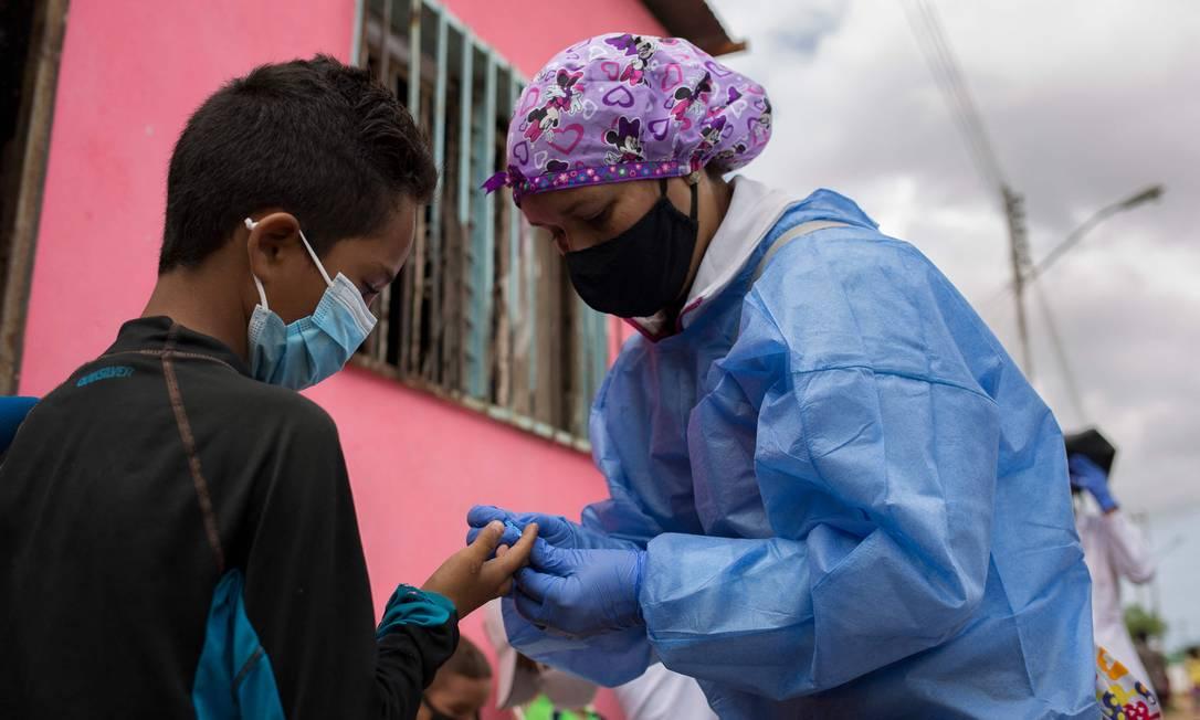 Voluntária médica da organização Médicos Sem Fronteiras (MSF) coleta uma amostra de sangue de um paciente para fazer o teste de malária na Venezuela, em março de 2021 Foto: PEDRO RANCES MATTEY / AFP