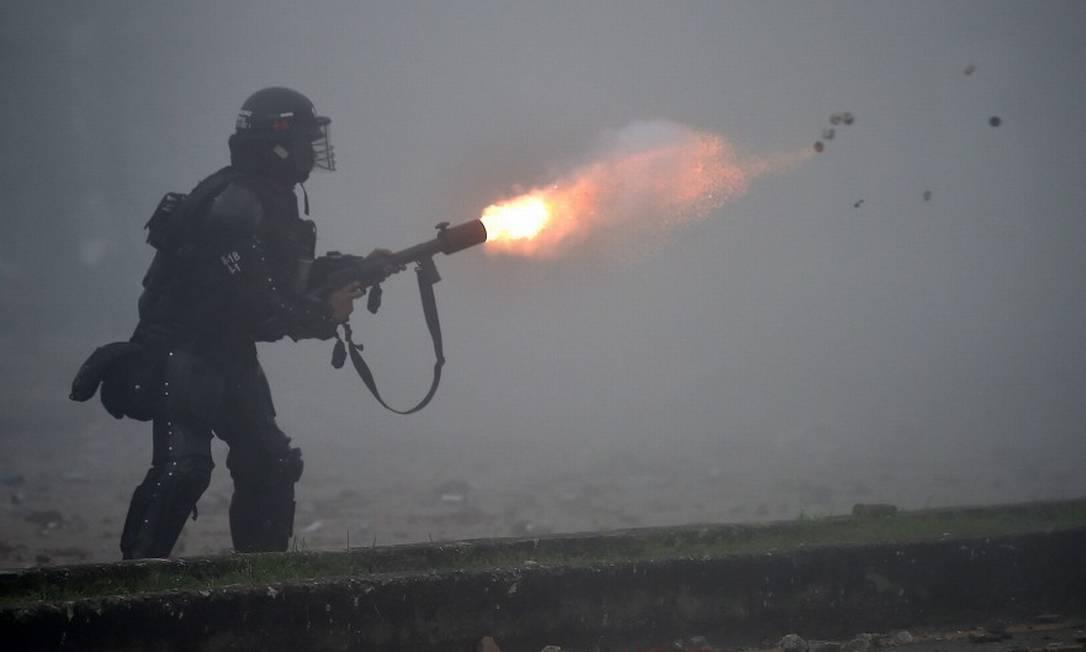 Policial da tropa de choque lança gás lacrimogêneo contra manifestantes na cidade de Cali Foto: LUIS ROBAYO / AFP/3-5-21