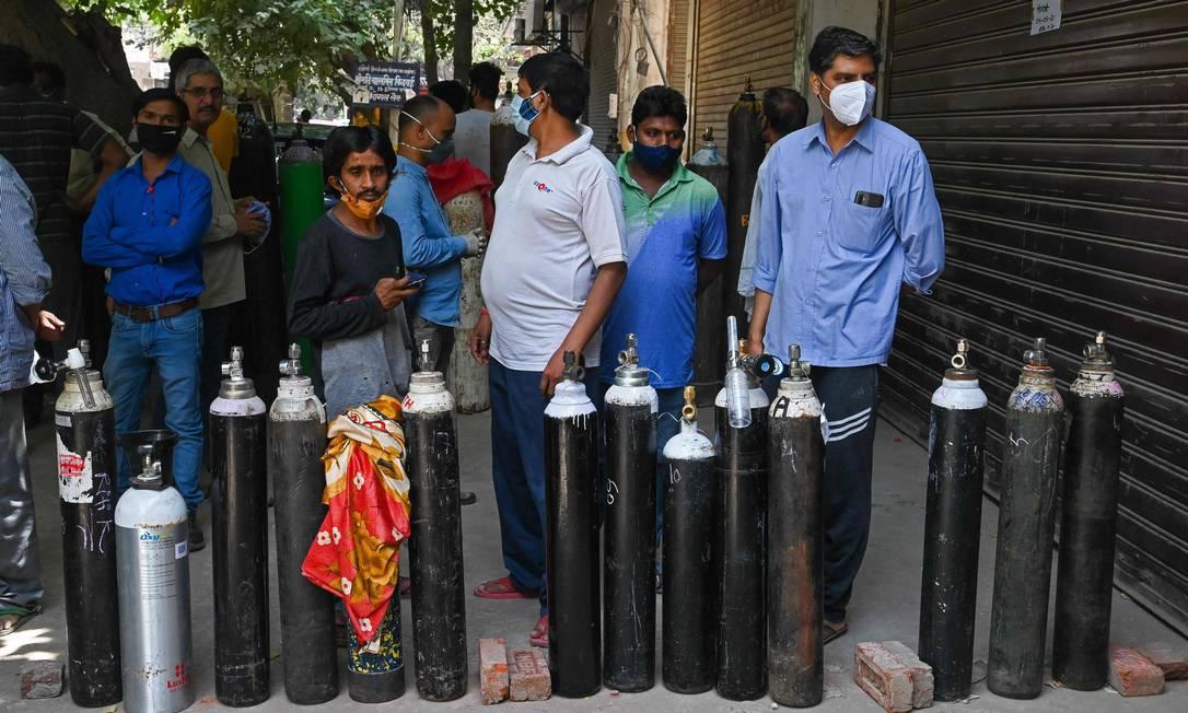 Familiares de pessoas com Covid-19 enfrentam longas filas para recarregar cilindro de oxigênio para tratamento domiciliar Foto: PRAKASH SINGH / AFP