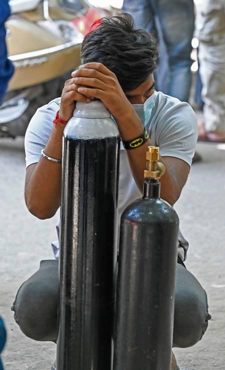 Homem descansa apoiado em cilindro de oxigênio à espera para reabastê-lo Foto: PRAKASH SINGH / AFP
