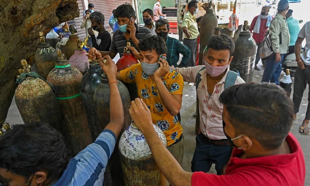 Indianos precisam pagar empresas privadas para recarregar cilindros de oxigênio para tratar familiares em casa Foto: PRAKASH SINGH / AFP