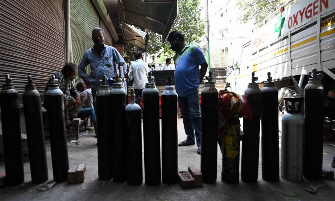 Pessoas esperam para reabastecer seus cilindros de oxigênio para os pacientes com coronavírus COVID-19 em quarentena domiciliar em um centro de recarga privado em Nova Delh Foto: MONEY SHARMA / AFP