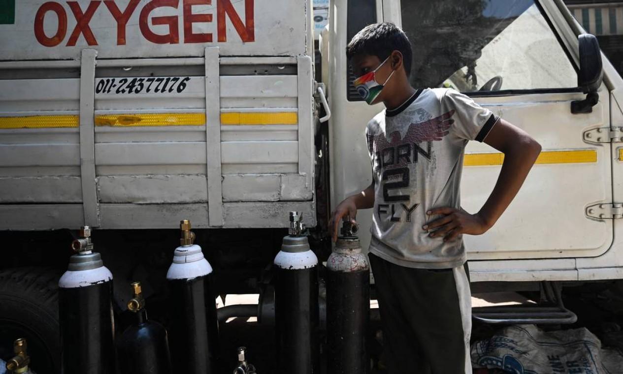 Jovem espera para reabastecer cilindros de oxigênio para os pacientes com coronavírus em quarentena domiciliar, em um centro de recarga privado, em Nova Delhi Foto: MONEY SHARMA / AFP