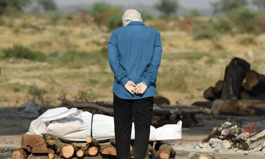Homem observa corpo de parente morto pela Covid-19 enquanto aguarda cremação Foto: SANJAY KANOJIA / AFP