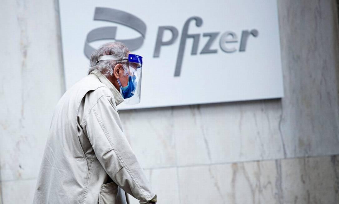 De máscara, homem caminha em frente à sede da Pfizer, em Nova York Foto: KENA BETANCUR / AFP/11-3-21
