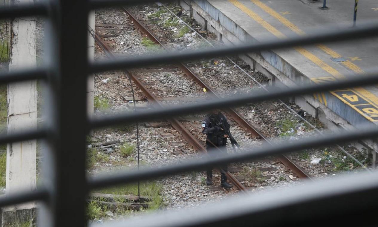 Polícial progride por trilhos do trem na estação Triagem. A operação foi suspensa Foto: Fabiano Rocha / Agência O Globo