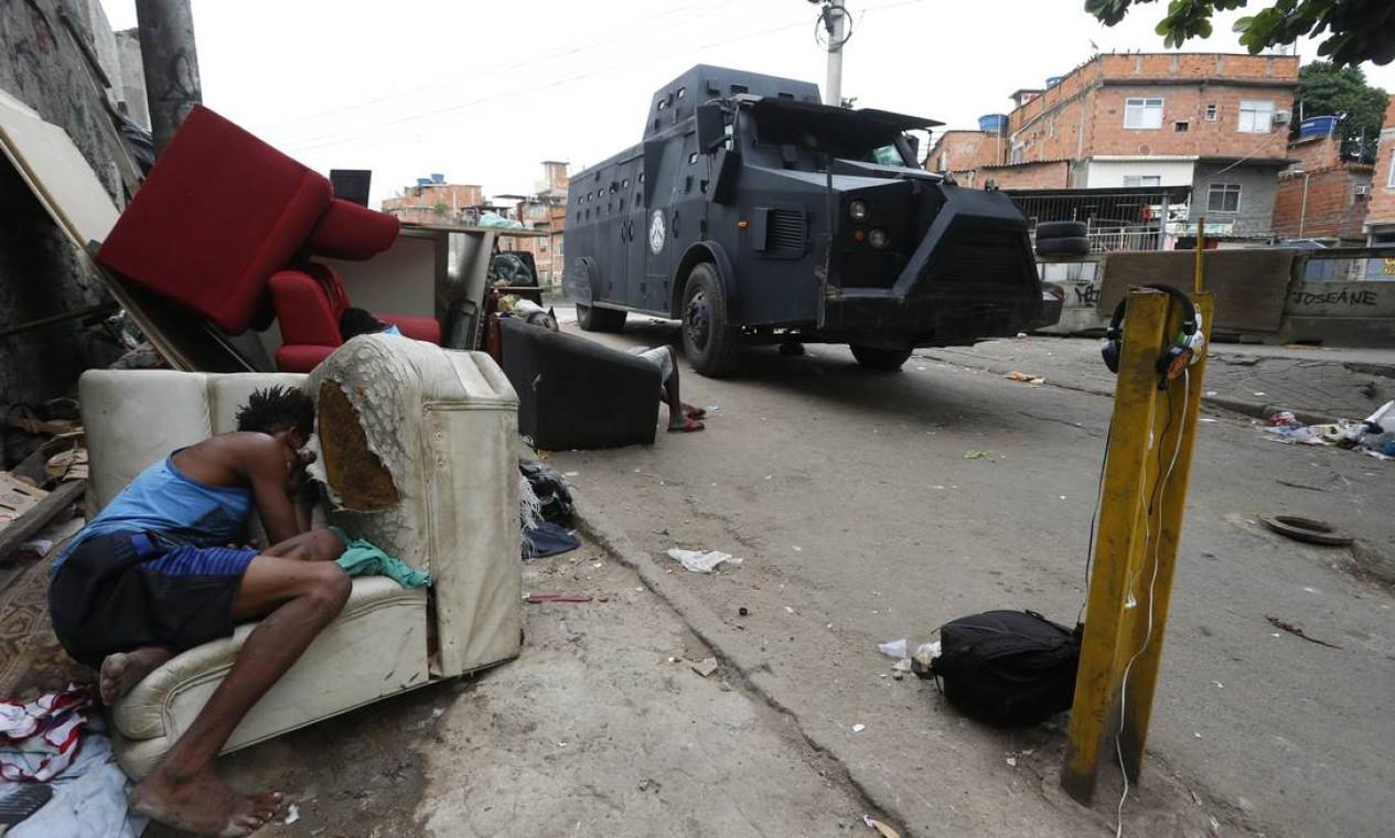 Pessoas em situação de rua dormem em mobília abandonada na rua enquanto passa o blindado da polícia Foto: Fabiano Rocha / Agência O Globo