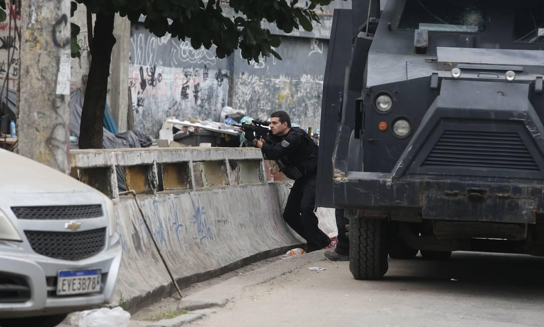 Protegido por mureta, policial troca tiros com bandidos no Jacarezinho Foto: Fabiano Rocha / Agência O Globo