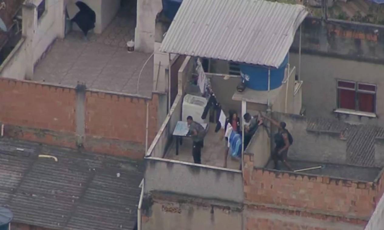 Imagem aérea do Globocop, da TV Globo, flagra criminosos fortemente armados fugindo da polícia e invadindo casas na comunidade do Jacaré Foto: Reprodução / TV Globo
