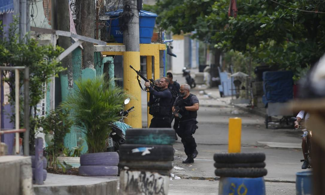 Policiais andam por rua do Jacarezinho com barricada para evitar acesso de veículos Foto: Fabiano Rocha / Agência O Globo