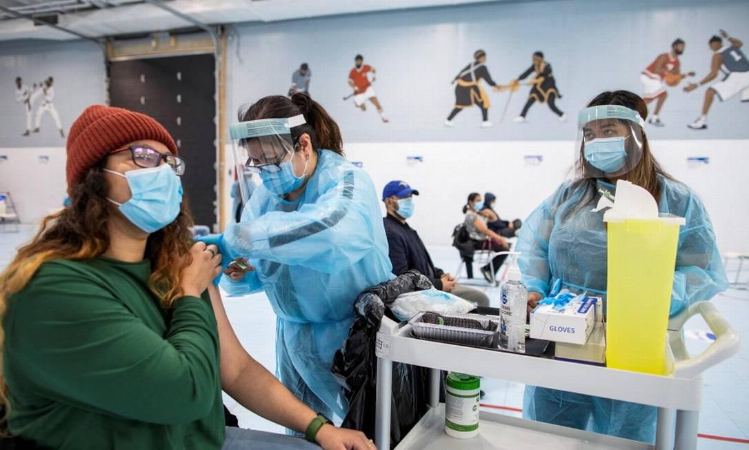 Profissionais da saúde administram vacina da Pfizer-BioNTech no Canadá Foto: CARLOS OSORIO / REUTERS/4-5-21