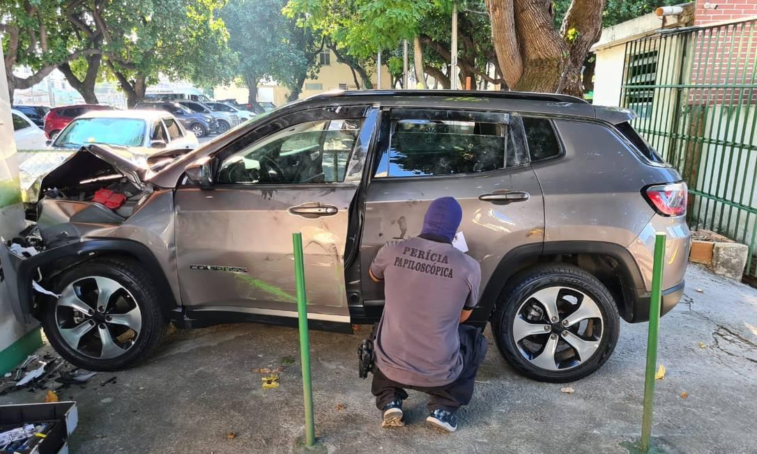 Policial faz perícia em carro recuperado pela polícia após ação na Penha Foto: Marcos Nunes / Agência O Globo