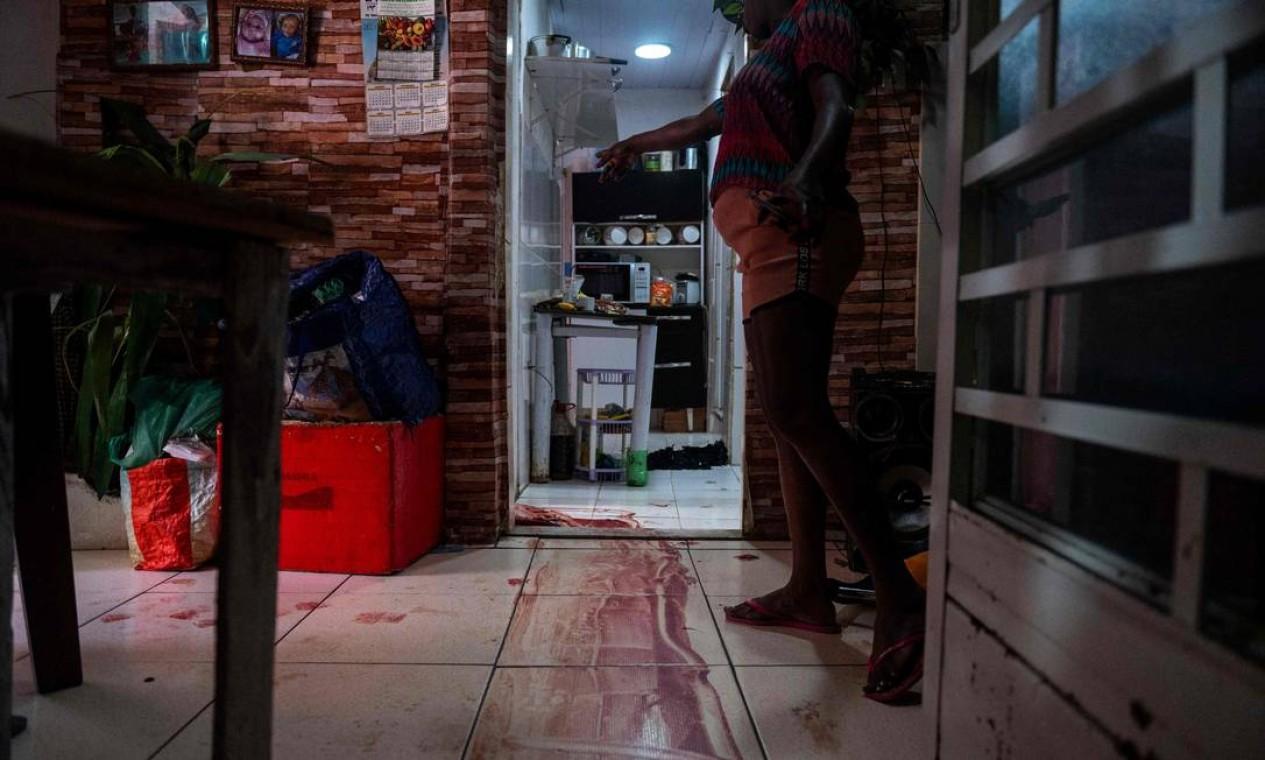 Mulher mostra marcas deixadas pela execução de um suspeito que fugia da polícia. A cena foi testemunada por uma criança de 9 anos Foto: Mauro Pimentel / AFP