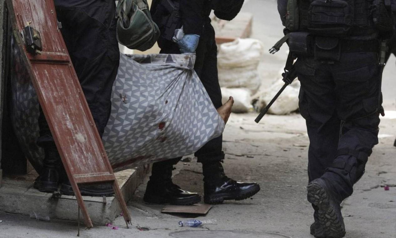 Policial carrega corpo durante ação no Jacarezinho Foto: Ricardo Moraes / Reuters
