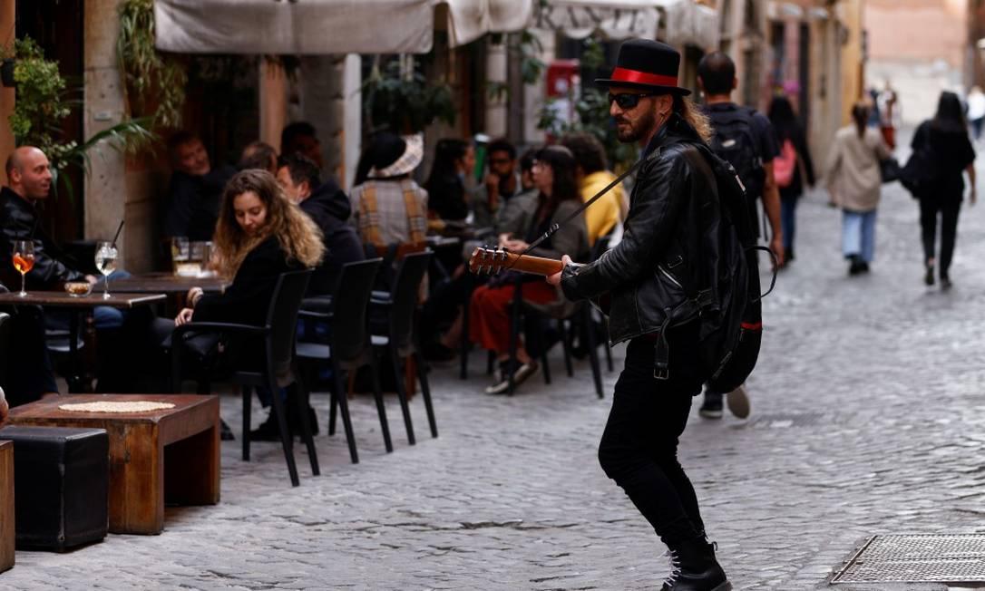 Homem toca violão em frente a fregueses de restaurantes em Roma; com o alívio das restrições, boa parte da Itália se tornou uma 'zona amarela' e restaurantes puderam voltar a servir clientes em espaços abertos Foto: GUGLIELMO MANGIAPANE / REUTERS/26-4-21