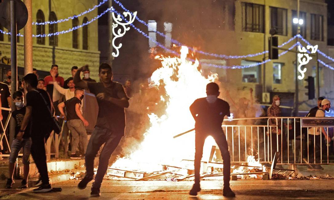 Manifestantes palestinos lançam pedras contra forças de segurança israelenses em Jerusalém Foto: EMMANUEL DUNAND / AFP/8-5-21