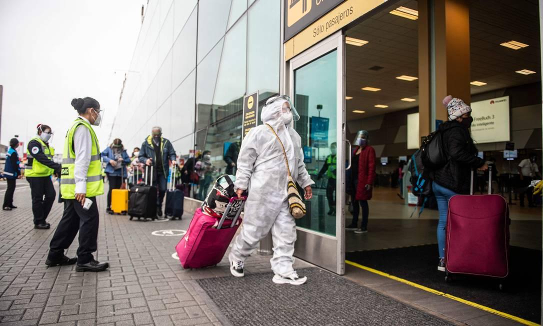 Passageiro entra no Aeroporto Internacional Jorge Chavez, em Callao, no Peru, vestindo traje de proteção, escudo facial e máscara contra a Covid-19 Foto: ERNESTO BENAVIDES / AFP
