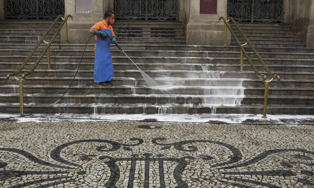Funcionário da Comlurb higieniza as escadarias do Teatro Municipal com sabão, cloro e desinfetante Foto: Márcia Foletto