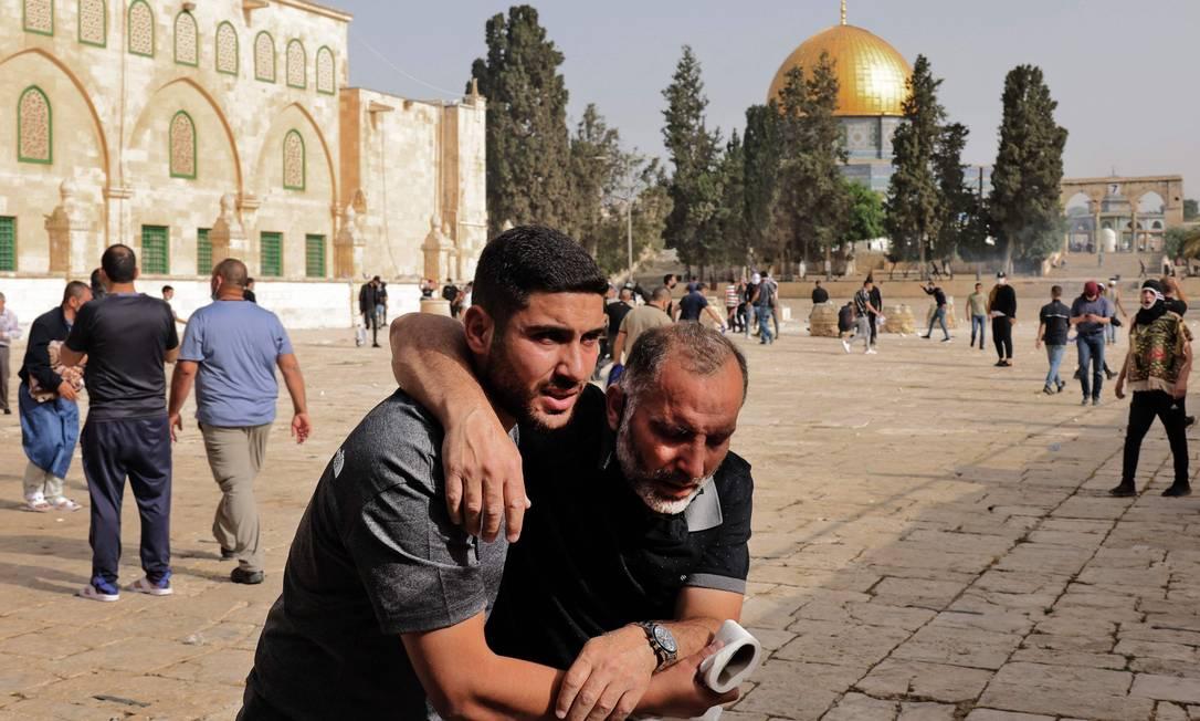 Palestino ajuda hmem ferido durante conflito com a polícia israelense na Esplanada das Mesquitas Foto: AHMAD GHARABLI / AFP