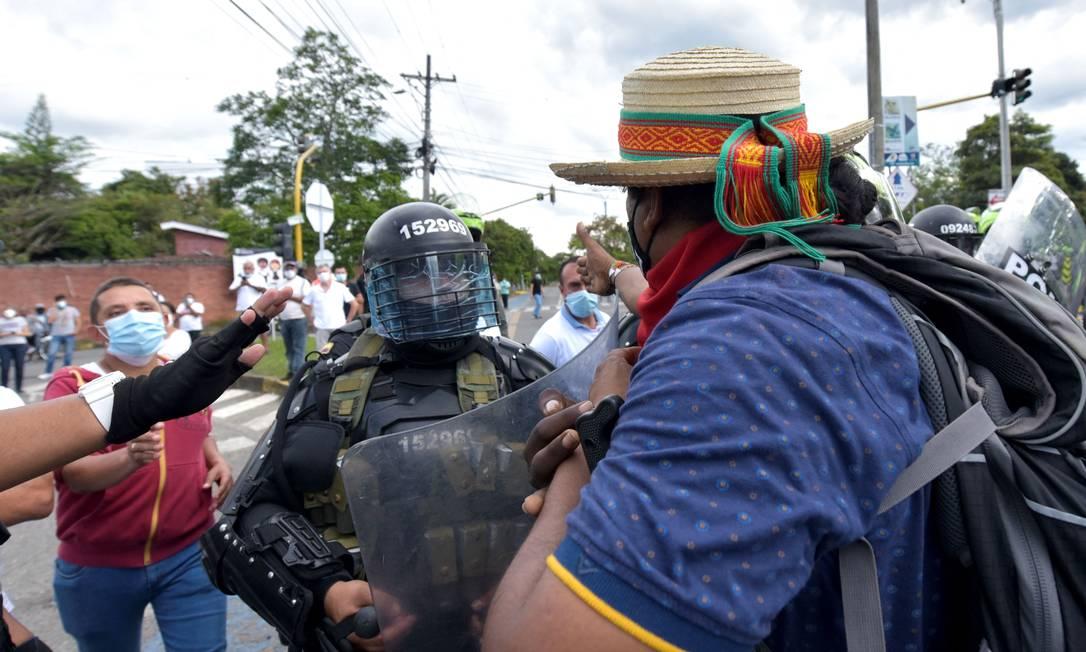 Um policial se posiciona entre indígenas e manifestantes que se opõem a bloqueios durante protestos em Cali, Colômbia Foto: LUIS CARLOS AYALA / AFP