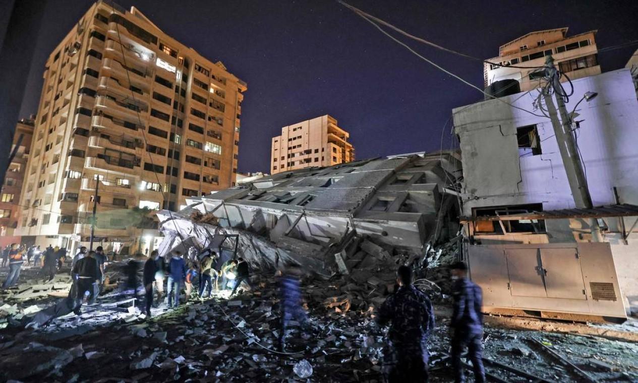 Pessoas em volta de um prédio derrubado após ataque aéreo israelense na Faixa de Gaza, em 11 de maio de 2021 Foto: MAHMUD HAMS / AFP
