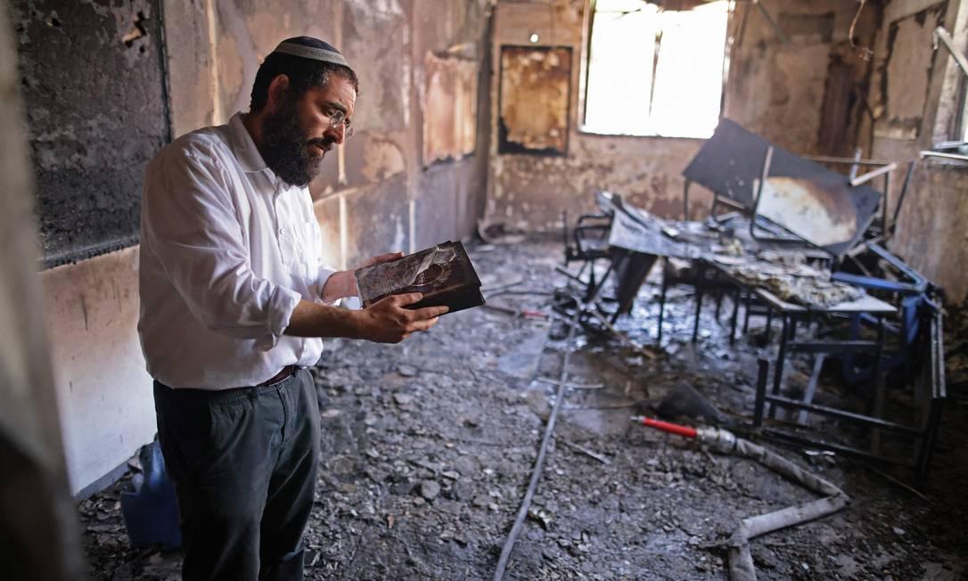 Um rabino inspeciona os danos dentro de uma escola religiosa incendiada na cidade israelense de Lod, perto de Tel Aviv Foto: AHMAD GHARABLI / AFP