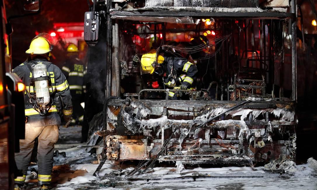 Bombeiros israelenses verificam um ônibus queimado na cidade israelense de Holon, perto de Tel Aviv Foto: AHMAD GHARABLI / AFP