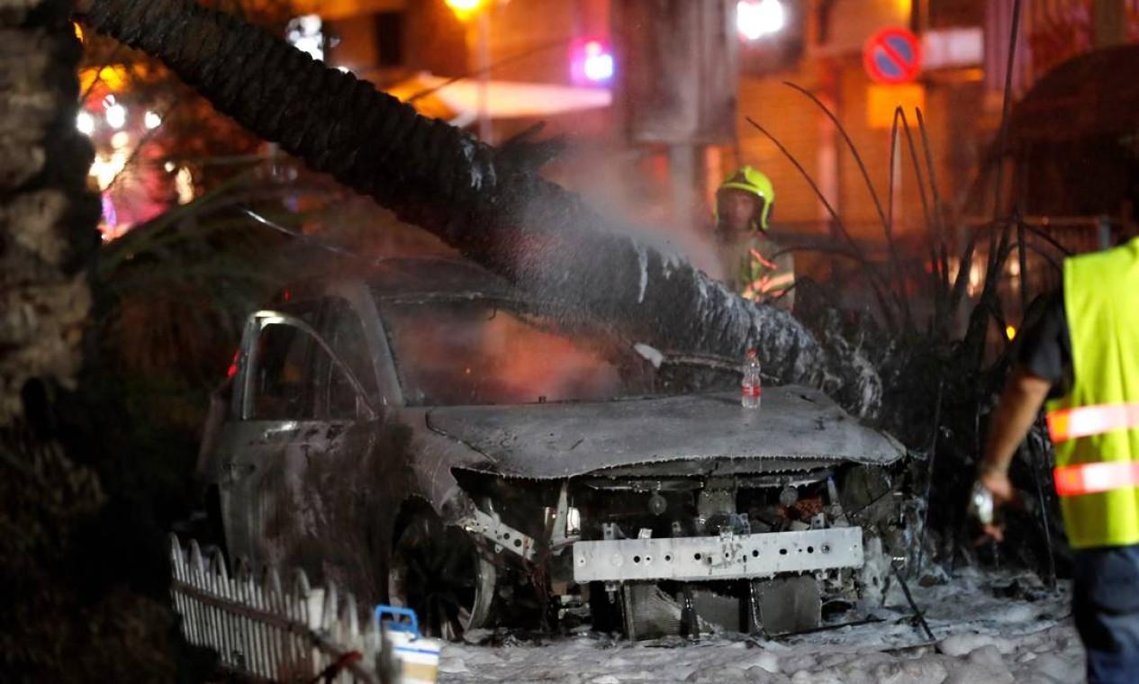 Bombeiros israelenses extinguem carros em chamas na cidade de Holon, perto de Tel Aviv Foto: AHMAD GHARABLI / AFP