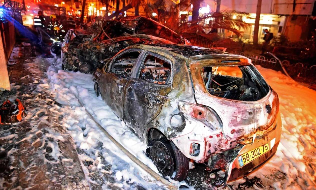 Veículos queimados são vistos na cidade de Holon, perto de Tel Aviv Foto: AHMAD GHARABLI / AFP