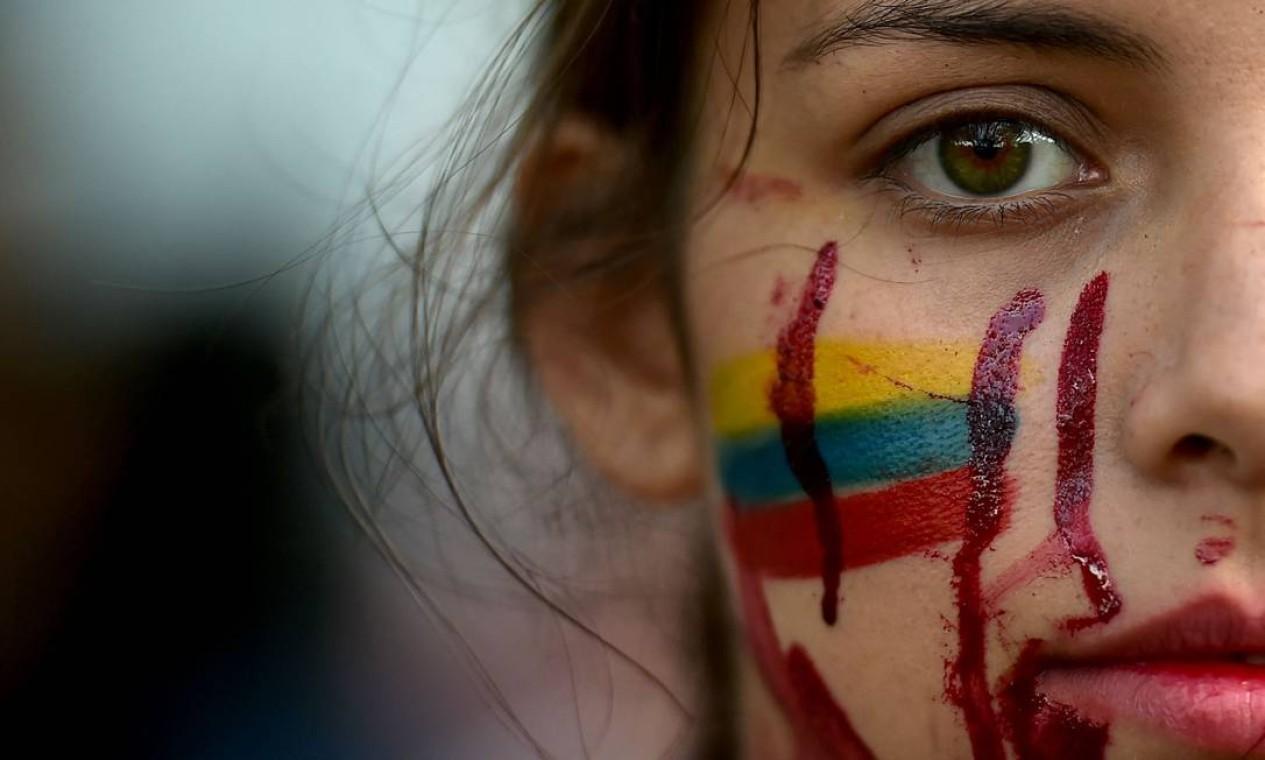 Estudante protesta contra assassinatos promovidos pelo estado colombiano para combater protestos antigovernamentais em Cali, Colômbia. Pelo menos, 42 pessoas, incluindo um oficial uniformizado, morreram nos confrontos entre forças de segurança e manifestantes Foto: LUIS ROBAYO / AFP - 12/05/2021