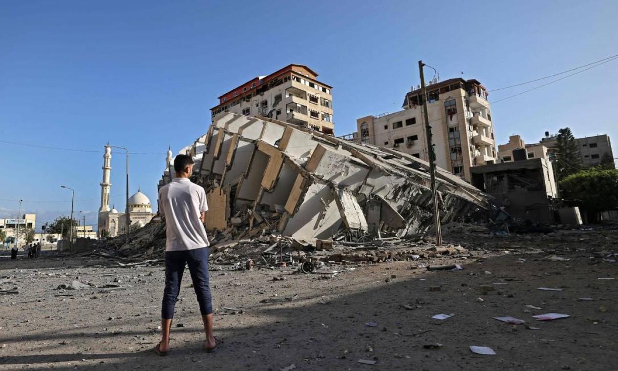 Um homem palestino olha para um prédio destruído na Cidade de Gaza, após uma série de ataques aéreos israelenses à Faixa de Gaza Foto: MOHAMMED ABED / AFP