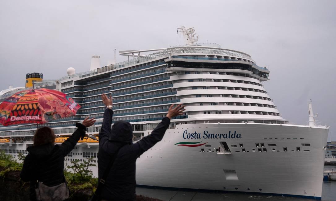 Pessoas acenam para o navio Costa Smeralda, no porto da cidade italiana de Savona Foto: MARCO BERTORELLO / AFP