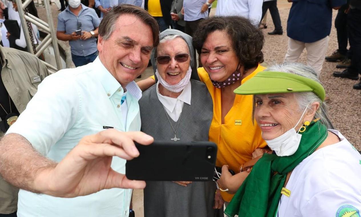 Bolsonaro faz selfies com idosas que usam máscara de proteção no queixo Foto: Isac Nóbrega / PR