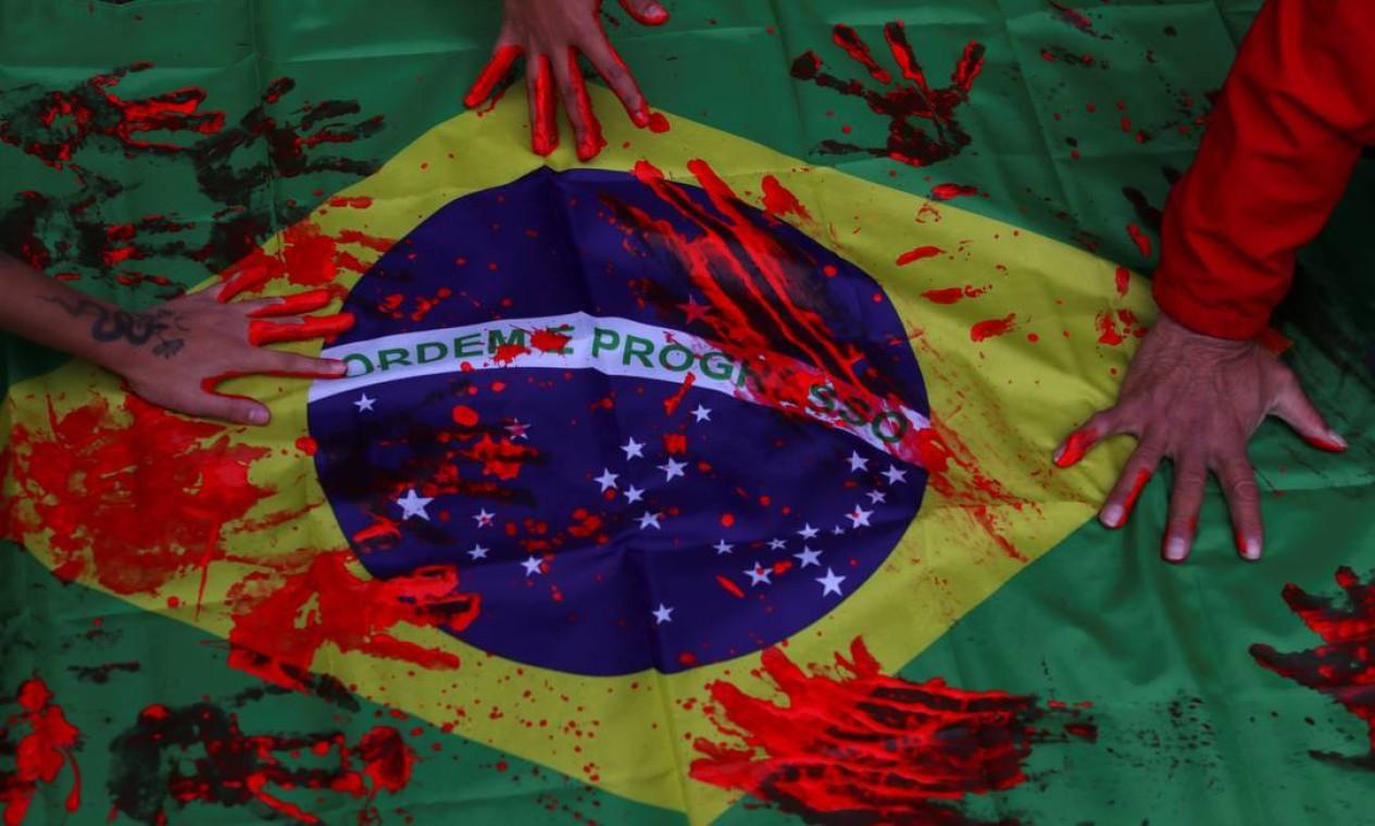 Ativistas tingem bandeira do Brasil usando as mãos pintadas com tinta vermelha em protesto contra a ação policial, considarada a mais letal da história do Rio, realizada na favela do Jacarezinho Foto: AMANDA PEROBELLI / REUTERS