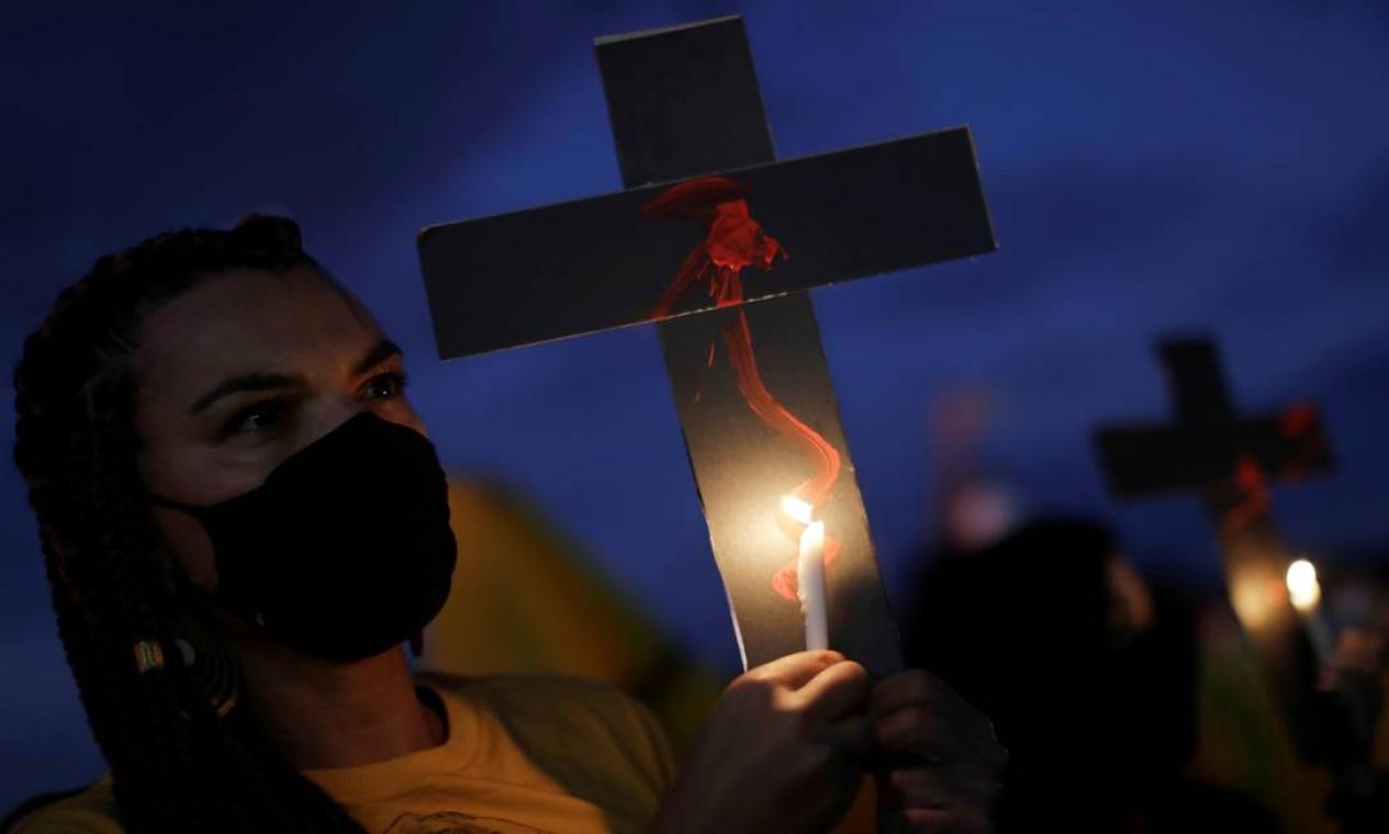 Manifestante segura uma vela e uma cruz durante um protesto contra o racismo e a violência policial em Brasília. Atos semelhantes foram registrados em diversas capitais do Brasil, com Rio e São Paulo Foto: UESLEI MARCELINO / REUTERS