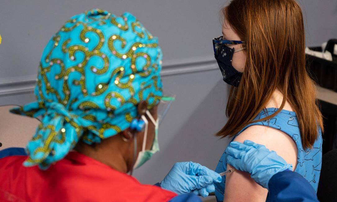 Adolescente de 13 anos recebe vacina contra a Covid-19 na clínica de vacinação em Fairfax, Virgínia, em 13 de maio de 2021 Foto: ANDREW CABALLERO-REYNOLDS / AFP