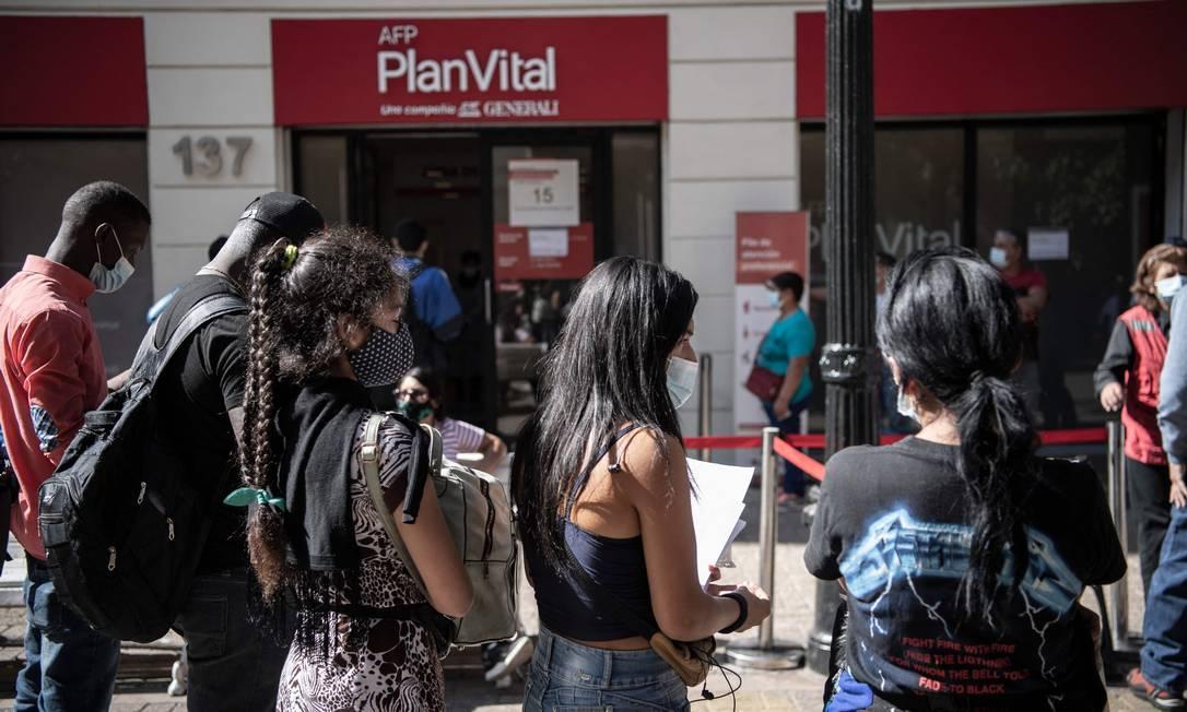 Chilenos fazem fila do lado de fora de uma Administradora de Fundos de Pensão (AFP) em Santiago para fazer a última retirada autorizada pelo Congresso, em abril Foto: MARTIN BERNETTI/26-4-2021 / AFP