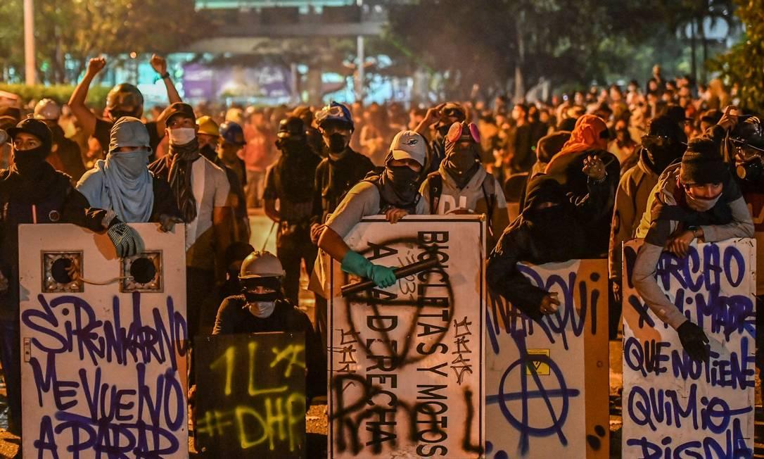 Manifestantes se reunem com escudos improvisados durante novo protesto contra o governo de Duque, realizado no domingo em Medellin Foto: JOAQUIN SARMIENTO / AFP