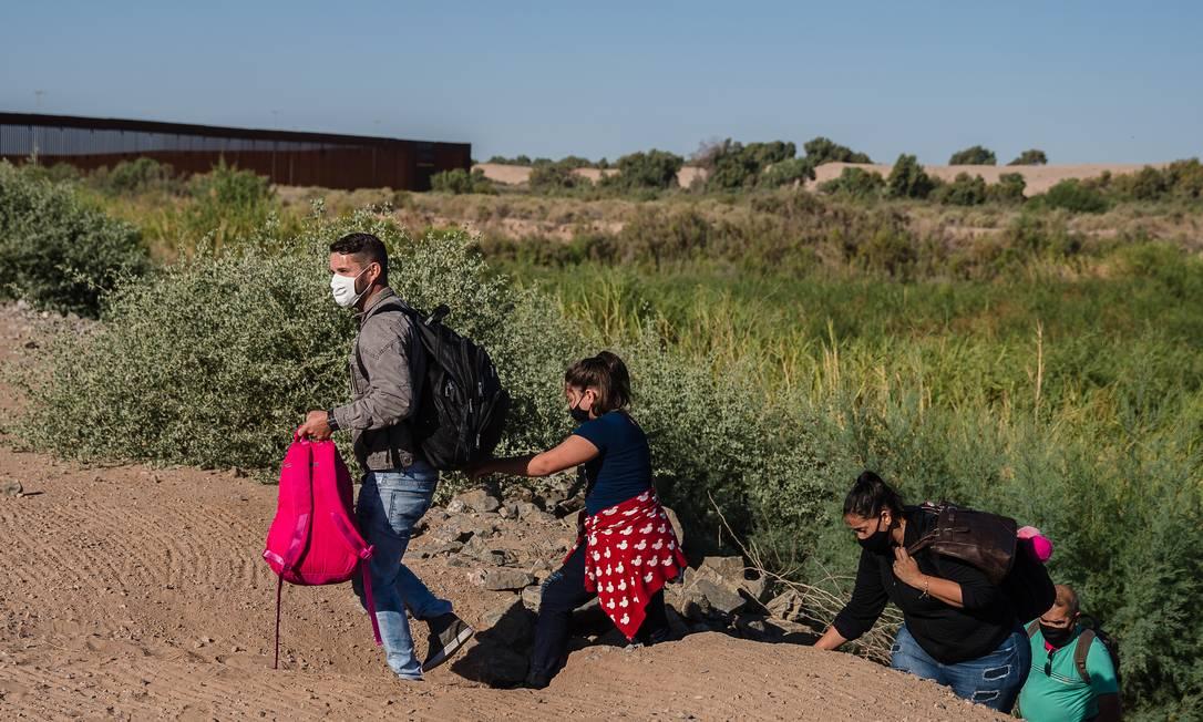 Uma família brasileira atravessa barragem em direção ao muro da fronteira em Yuma, Arizona Foto: ARIANA DREHSLER / NYT