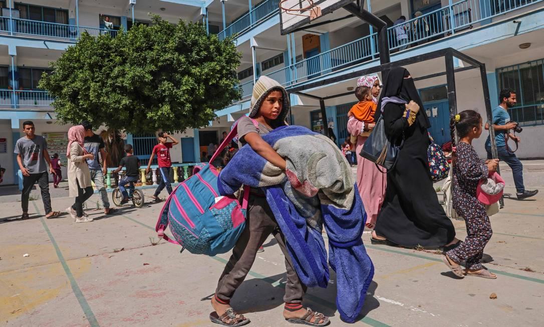 Palestinos deslocados buscam abrigo em escola da ONU na cidade de Rafah, no Sul do enclave Foto: SAID KHATIB / AFP