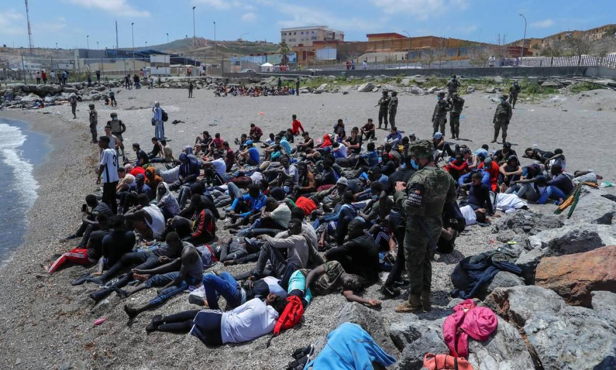 Militares espanhóis cercam cidadãos marroquinos, depois que milhares de marroquinos nadaram pela fronteira hispano-marroquina Foto: JON NAZCA / REUTERS