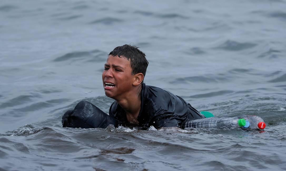Menino marroquino chora nadando usando garrafas como flutuadores, próximo à cerca entre a fronteira hispano-marroquina, em Ceuta, Espanha Foto: JON NAZCA / REUTERS