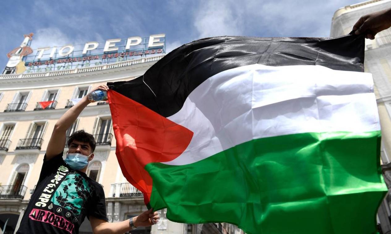 """Homem segura uma bandeira palestina durante uma manifestação que marca o 73º aniversário da """"Naqba"""" em Madrid. A """"Naqba"""", (Dia da Catástrofe) refere-se ao dia 15 de maio de 1948 , quando o moderno Estado de Israel foi estabelecido após a guerra árabe-israelense, que levou ao deslocamento de centenas de milhares de palestinos Foto: GABRIEL BOUYS / AFP - 15/05/2021"""