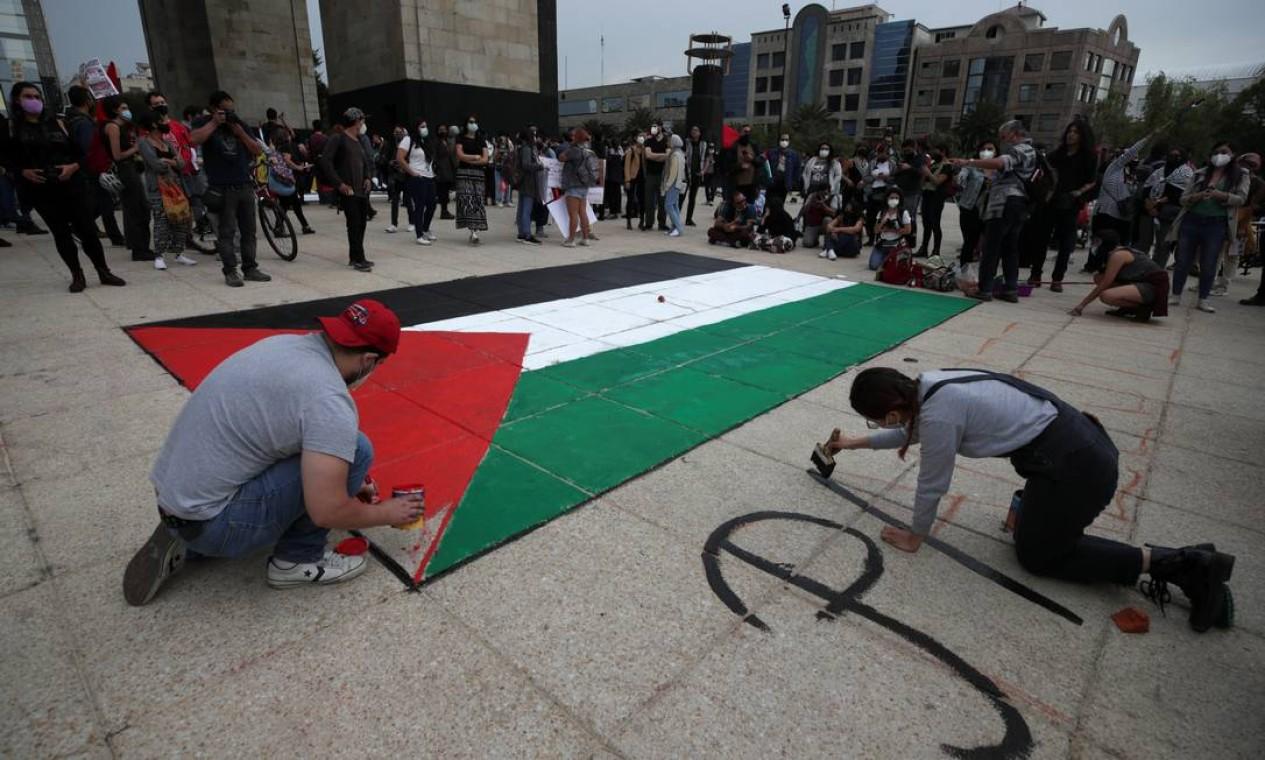 """Um homem pinta uma bandeira palestina no chão perto do Monumento à Revolução enquanto uma mulher escreve """"Palestina Livre"""", na Cidade do México, México Foto: HENRY ROMERO / REUTERS - 15/05/2021"""